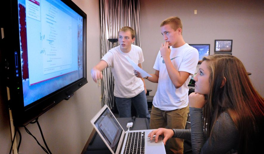 Pequea Valley students from left; Terry Disanto, Connor Horst and Rhiannon Peachey solve a geometry problem on a smart TV at Pequea Valley High School in Lancaster, Pa. (AP Photo/LNP Media Group, Blaine Shahan)