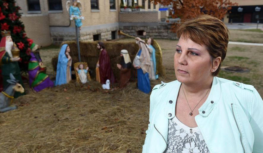 """In this Tuesday, Dec. 23, 2014 photo, Dessa Blackthorn, of Mountain Home, Ark., poses for a photo in front of the nativity scene displayed on the Baxter County, Ark., courthouse lawn. The disclaimer at the Baxter County Courthouse nativity scene isn't protecting it from a lawsuit challenging its placement on public property. J.G. """"Gerry"""" Shulze, a Little Rock lawyer, confirmed Tuesday a lawsuit has been submitted to the U.S. District Court for Western Arkansas on behalf of the American Humanist Association and Baxter County resident Dessa Blackthorn, The Baxter Bulletin reported. (AP Photo/The Baxter Bulletin, Kevin Pieper)"""