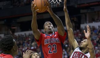 Arizona forward Rondae Hollis-Jefferson (23) take a shot as UNLV guard Jelan Kendrick (22) defends during an NCAA college basketball game Tuesday, Dec. 23, 2014, in Las Vegas. (AP Photo/Eric Jamison)
