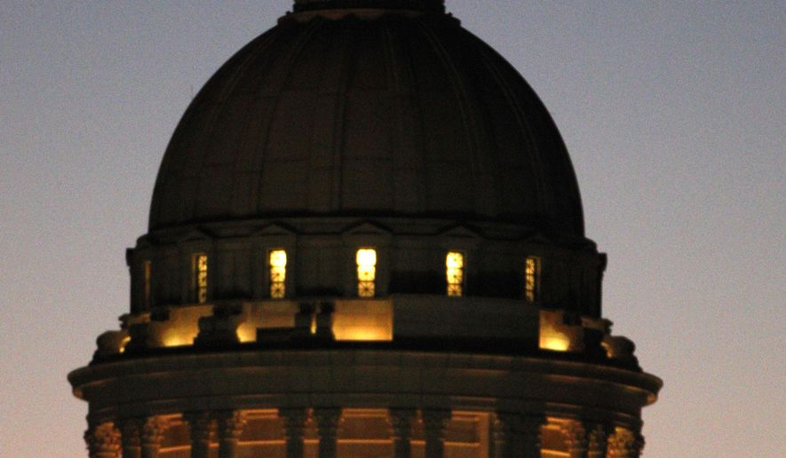 FILE - In this Thursday, Nov. 10, 2011 file photo, the dome of the Oklahoma Capitol is illuminated as the sky darkens in Oklahoma City. The Oklahoman reported Tuesday that the Oklahoma Capitol dome has significant cracks in the exterior of the dome, but not in the structural part of the dome. (AP Photo/Sue Ogrocki, File)