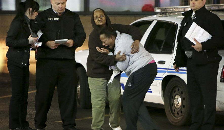 Toni Martin, front center, cries out on Wednesday, Dec. 24, 2014, as she talks to police at the scene where she says her son was fatally shot Tuesday at a gas station in Berkeley, Mo. Authorities did not immediately identify the man who was shot. But the St. Louis Post-Dispatch reported that Toni Martin, said he was her son, Antonio Martin. (AP Photo/St. Louis Post-Dispatch, David Carson)