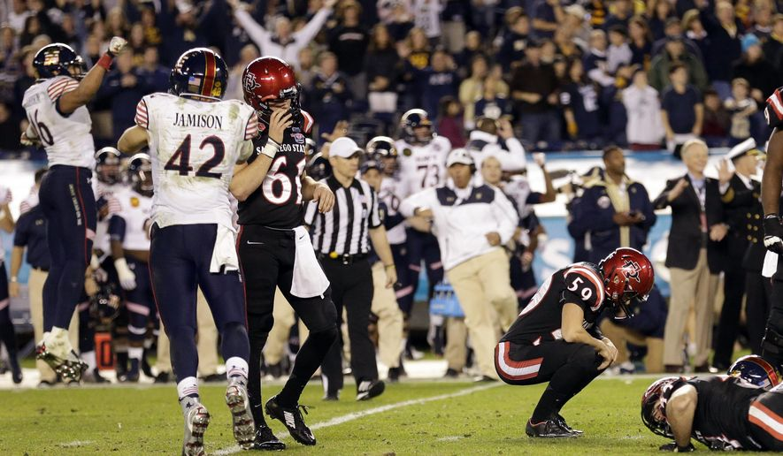 San Diego State place kicker Donny Hageman (59) reacts after missing a field goal that could have won the game against Navy as Navy safety George Jamison, (42) and San Diego State long snapper Hunter Christensen (61) look on during the second half of the Poinsettia Bowl NCAA college football game Tuesday, Dec. 23, 2014, in San Diego. Navy won 17-16. (AP Photo/Gregory Bull)