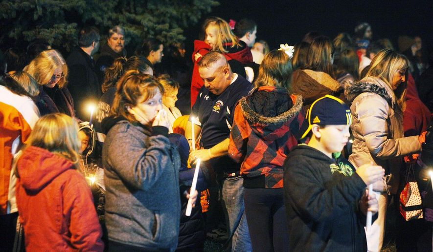 A vigil was held in honor of Samantha N. Carpenter, 10, Tuesday night, Dec. 23, 2014, at National Trail School, where she was a straight-A student. Her classmates, their parents and staff gathered outside the school. Samantha was shot and killed by her mother's live-in boyfriend, Brian E. Harleman, who killed himself after critically shooting her mother, Catherine L. Gessman. (AP Photo/Dayton Daily News, Jarod Thrush)