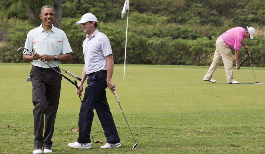 President Barack Obama, left, plays golf with White House aide Joe Paulsen, and Malaysian Prime Minister Najib Razak, right in pink, Wednesday, Dec. 24, 2014, at Marine Corps Base Hawaii's Kaneohe Klipper Golf Course in Kaneohe, Hawaii during the Obama family vacation. (AP Photo/Jacquelyn Martin)