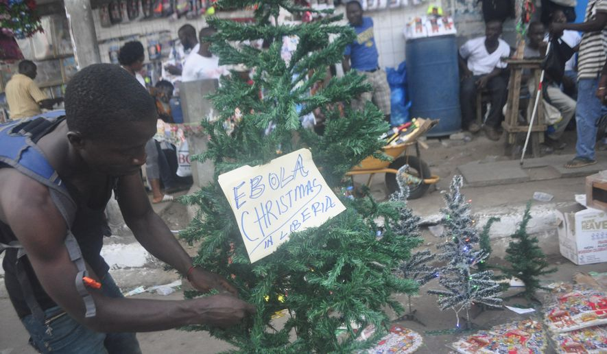 A Liberian man arranges a Christmas tree at a shop in Monrovia, Liberia, Wednesday, Dec. 24, 2014. The deadly Ebola epidemic in Sierra Leone means no festive parties at the beach, no carolers singing at night. Authorities this year have banned any activities that could further the spread of the highly contagious virus now blamed for killing more than 7,000 people in West Africa over the past year. (AP Photo/Abbas Dulleh)