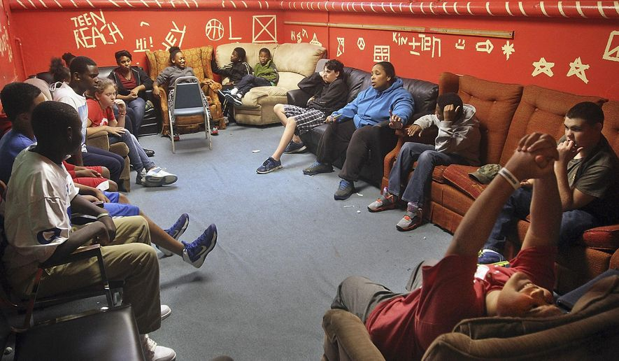 In this Sept. 12, 2014 photo, program assistant LaChell Wigfall, center right, leads a discussion during a Teen Reach program session in Quincy, Ill. The program for at-risk students ages 6 to 17, provides help from a team of adults and fellow students each weekday from 3 to 6:30 p.m. Teen Reach has been operating in Quincy since 1998, and provides assistance with homework, activities, and meals for the participants. (AP Photo/The Quincy Herald-Whig, Michael Kipley)