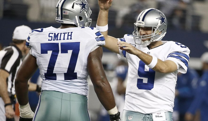 Dallas Cowboys quarterback Tony Romo (9) celebrates with Tyron Smith (77) after throwing a touchdown pass to Jason Witten during the second half of an NFL football game against the Indianapolis Colts, Sunday, Dec. 21, 2014, in Arlington, Texas. (AP Photo/Brandon Wade)