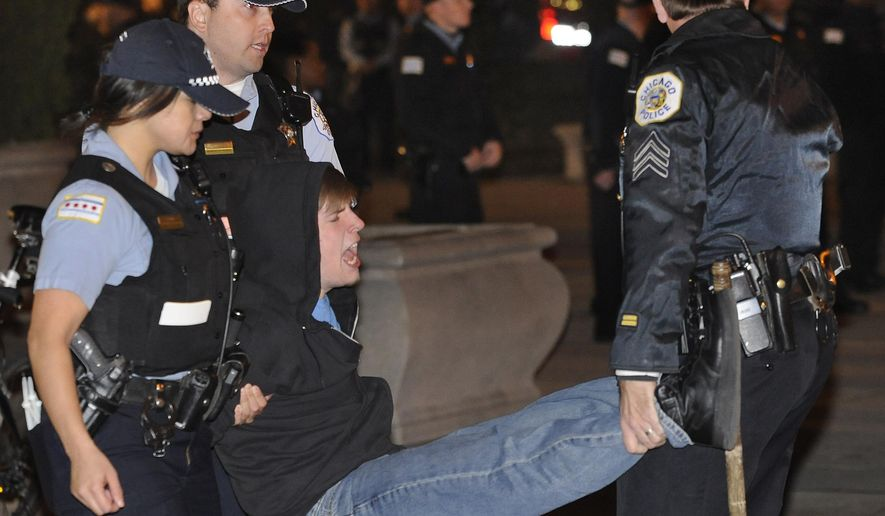 """FILE - In this Oct. 23, 2011 file photo, a protester gets arrested during an Occupy Chicago march and protest in Grant Park in Chicago. A state appeals court ruled Tuesday, Dec. 23, 2014 that a Chicago curfew law invoked to arrest Occupy protesters at the park in 2011 doesn't violate free speech rights, declaring the First Amendment """"does not guarantee the right to employ every conceivable method of communication at all times and in all places."""" The ruling by a three-judge panel of the 1st District Appellate Court reverses a lower-court finding that the 11 p.m. to 6 a.m. curfew at the 319-acre Grant Park violated protesters' constitutional rights. (AP Photo/Paul Beaty, File)"""