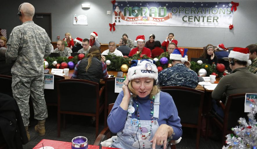 Volunteer Patty Shook takes a phone call from a child asking where Santa is and when he will deliver presents to her home, inside a phone-in center during the annual NORAD Tracks Santa Operation, at the North American Aerospace Defense Command, at Peterson Air Force Base, Colo., on Wednesday, Dec. 24, 2014. Patty and her husband, Bryan, who is retired from the Air Force, have been volunteering at NORAD each Christmas Eve for five years, fielding calls from children from all over the world eager to hear about Santa's progress. (AP Photo/Brennan Linsley)