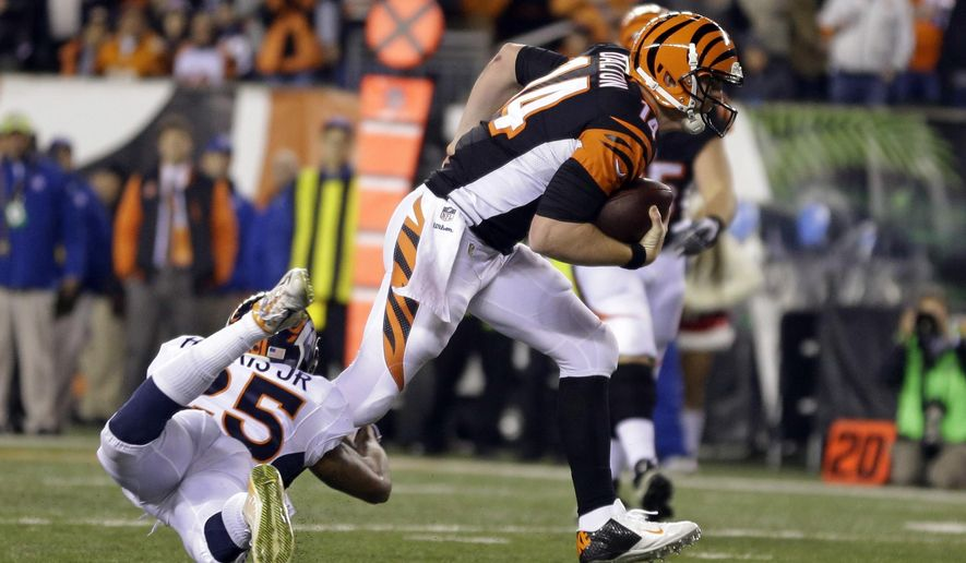 Cincinnati Bengals quarterback Andy Dalton (14) is tackled by Denver Broncos cornerback Chris Harris (25) during the first half of an NFL football game Monday, Dec. 22, 2014, in Cincinnati. (AP Photo/Michael Conroy)