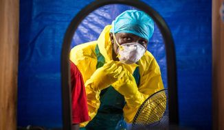 In this Oct. 16, 2014, file photo, a health care worker dons protective gear before entering an Ebola treatment center in Freetown, Sierra Leone. In a letter published online Wednesday, Dec. 24. 2014, by the New England Journal of Medicine, doctors report that the Ebola death rate seems to have fallen even though there are no specific medicines or vaccines to fight the virus. (AP Photo/Michael Duff, File)