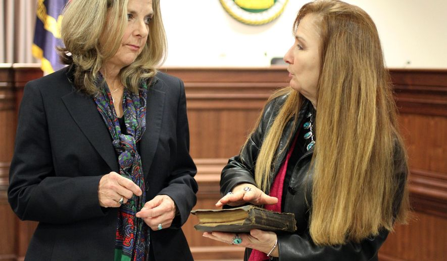 In this Dec. 1, 2014 photo provided by Buncombe County PR, County Commissioner Ellen Frost speaks with family friend Lynn Brogan, who's holding a Bible that was used in Frost's swearing-in ceremony, in Raleigh, N.C. An inscription written in the Bible in 1900 traces its link from Edith Vanderbilt to the woman who's the namesake of Lillian's List. (AP Photo/Buncombe County PR, Cataldo Perrone)
