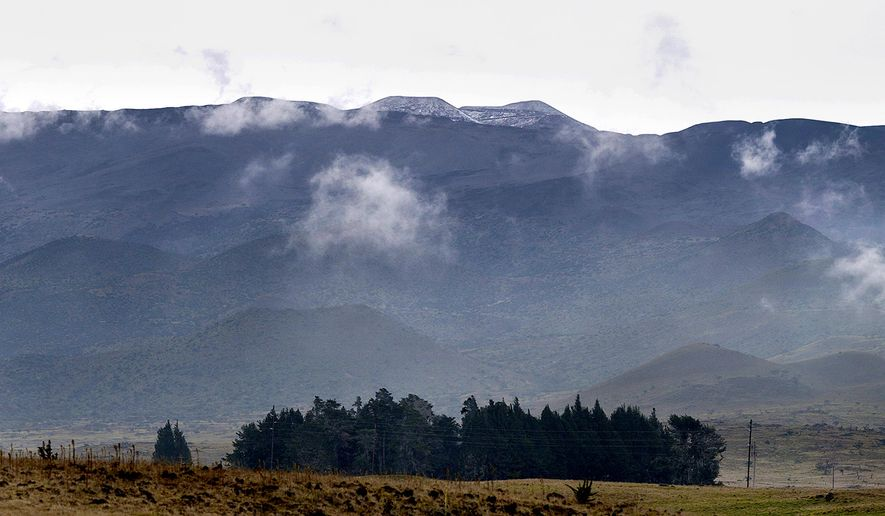 This Tuesday, Dec. 23, 2014 photo shows a dusting of snow on Mauna Kea on the Big Island of Hawaii. While snow on the mountains is common, a blizzard with significant accumulation is unusual. (AP Photo/Hawaii Tribune-Herald, Hollyn Johnson)