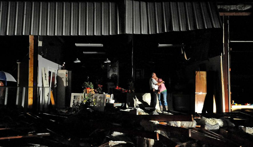 Jeff and Melissa McKenzie embrace in the ruins of their florist and gift shop store in Columbia, Miss., after a tornado ripped through the city Tuesday, Dec. 23, 2014. According to Marion County Emergency Management the tornado touched down around 2:30 p.m. Tuesday. (AP Photo/The Hattiesburg American, Eli Baylis)
