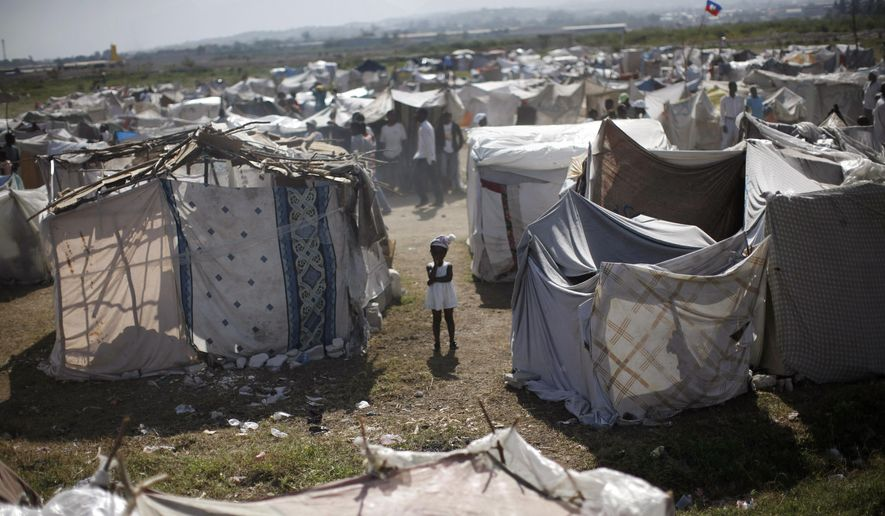 """FILE -  This Feb. 13, 2010, file photo shows a child standing among makeshift tents at a refugee camp for earthquake survivors in the Cite Soleil neighborhood of Port-au-Prince. A few hours before 19-year-old Britney Gengel was buried alive in the earthquake, she texted her parents her last dream: """"I want to move here and start an orphanage."""" Nearly five years later Gengel's father is fulfilling the dream of his late daughter. (AP Photo/Rodrigo Abd, File)"""