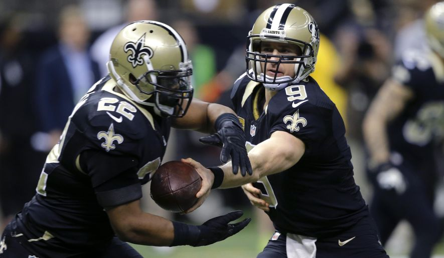 New Orleans Saints quarterback Drew Brees (9) hands off to running back Mark Ingram (22) in the first half of an NFL football game against the Atlanta Falcons in New Orleans, Sunday, Dec. 21, 2014. (AP Photo/Bill Haber)