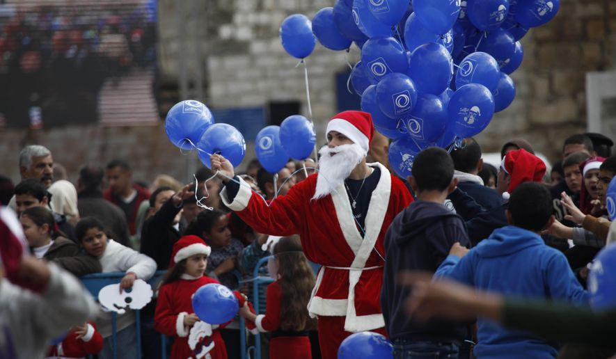 A Palestinian dressed as Santa Claus holds balloons at Manger Square, outside the Church of the Nativity, traditionally believed by Christians to be the birthplace of Jesus Christ, in the West Bank city of Bethlehem on Christmas Eve Wednesday, Dec. 24, 2014. (AP Photo/Majdi Mohammed)