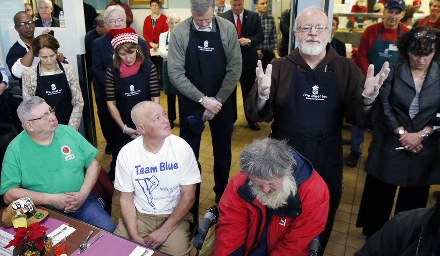 Massachusetts Gov.- elect Charlie Baker, standing center,  and Lt. Gov.-elect Karyn Polito, standing center left, bow their heads as Archbishop of Boston Sean O'Malley, standing center right, says a prayer before serving meals at the Pine Street Inn homeless shelter in Boston, Wednesday, Dec. 24, 2014. (AP Photo/Michael Dwyer)