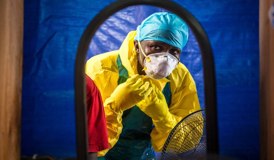 FILE - In this Oct. 16, 2014, file photo, a healthcare worker dons protective gear before entering an Ebola treatment center in Freetown, Sierra Leone. In a letter published online Wednesday, Dec. 24. 2014, by the New England Journal of Medicine, doctors report that the Ebola death rate seems to have fallen even though there are no specific medicines or vaccines to fight the virus. (AP Photo/Michael Duff, File)