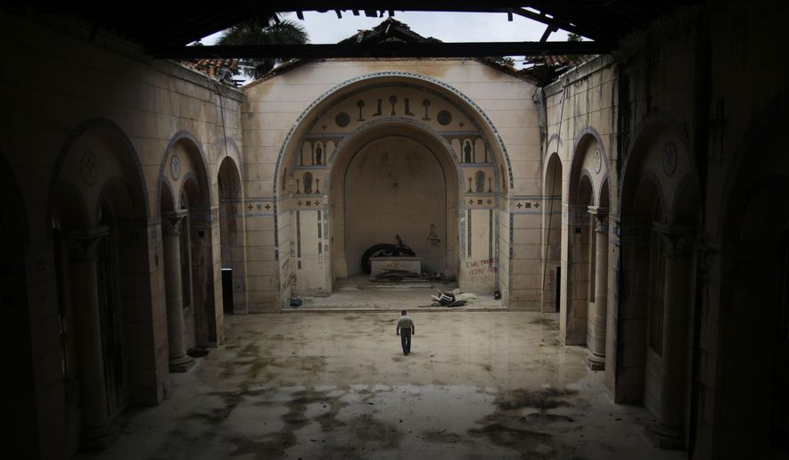 In this Dec. 1, 2014, a guard walks inside the chapel of the former University of Santo Thomas of Villanueva in Havana, Cuba. Since late 2009, President Raul Castro's government has been quietly returning some church property that was confiscated in the years after the Cuban revolution, including this chapel. The rest of the university property was not returned. (AP Photo/Ramon Espinosa)