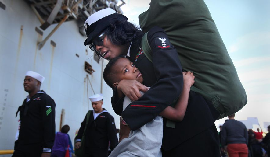 Shanita Frieson and son Anthony Black, 7, are reunited Wednesday, Dec. 24, 2014, in San Diego, Calif. The USS Peleliu arrived home to Naval Base San Diego from a six-month deployment on Wednesday, just in time to reunite hundreds of Navy families for the holidays. (AP Photo/U-T San Diego, Peggy Peattie)  NO SALES; COMMERCIAL INTERNET OUT