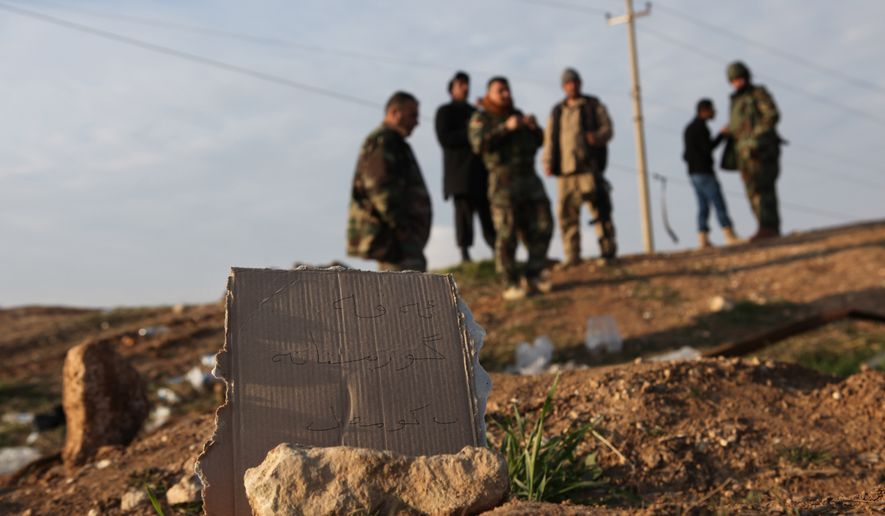 "In this Monday, Dec. 22, 2014 photo, Kurdish Peshmerga forces inspect a site marked in Kurdish with a sign reading, ""Kurdish mass grave,"" in Hardan village in northern Iraq. A handful of Yazidis who fled this tiny northern Iraqi hamlet when Islamic State militants overran it in August have returned after Kurdish fighters drove out the extremists in recent days. They want to learn the fate of hundreds of missing relatives and neighbors and they fear they know where they are: Four mounds of freshly dug dirt in nearby fields they believe are graves. (AP Photo/Dalton Bennett)"
