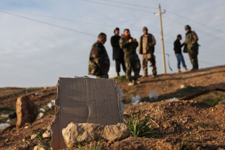 """In this Monday, Dec. 22, 2014 photo, Kurdish Peshmerga forces inspect a site marked in Kurdish with a sign reading, """"Kurdish mass grave,"""" in Hardan village in northern Iraq. A handful of Yazidis who fled this tiny northern Iraqi hamlet when Islamic State militants overran it in August have returned after Kurdish fighters drove out the extremists in recent days. They want to learn the fate of hundreds of missing relatives and neighbors and they fear they know where they are: Four mounds of freshly dug dirt in nearby fields they believe are graves. (AP Photo/Dalton Bennett)"""