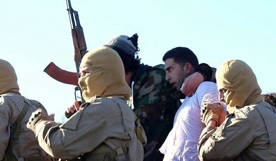 This image posted by the Raqqa Media Center of the Islamic State group, a militant extremist group, which has been authenticated based on its contents and other AP reporting, shows members of the Islamic State group with a captured pilot, center, wearing a white shirt in Raqqa, Syria, Wednesday, Dec. 24, 2014. Activists say that Islamic State fighters have shot down a warplane believed to be from the U.S.-led coalition over Syria. (AP Photo/Raqqa Media Center of the Islamic State group)