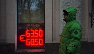 A man walks along the Boulevard Ring in downtown Moscow, Russia, Wednesday, Dec. 24, 2014 with a currency exchange office sign in a window. Russia's central bank made another move Wednesday to shore up the battered ruble, offering hard currency loans to companies and banks to help them service their debts. The bank said that borrowers could put their debt obligations as collateral against the loans. It's a major relief for the nation's companies and banks, who can't tap foreign capital markets to refinance their loans because of Western sanctions.  (AP Photo/Alexander Zemlianichenko)