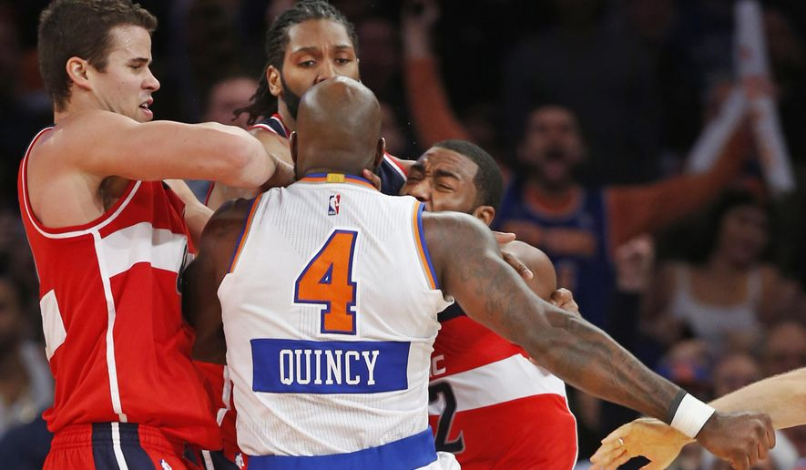 Washington Wizards forwards Kris Humphries, left, and Nene Hilario restrain New York Knicks forward Quincy Acy (4) who has his hand rolled into a fist, and Wizards guard John Wall (2) after Wall and Acy engaged in an on-court scuffle in the second half of an NBA basketball game at Madison Square Garden in New York, Thursday, Dec. 25, 2014. The Wizards defeated the Knicks 102-91. Acy was ejected from the game Wall was for called for a technical foul. (AP Photo/Kathy Willens)