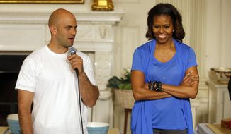"""FILE - In this June 12, 2104, file photo, first lady Michelle Obama stands with Sam Kass, White House Senior Policy Adviser for Nutrition Policy, before they make salads from vegetables harvested from the White House garden with area students in the State Dining Room of the White House in Washington. President Barack Obama's personal chef is leaving after nearly six years in which, unlike any assistant White House chef before him, he cooked up policy alongside his meals. Kass held the title of senior policy adviser for nutrition policy, which gave him a seat at the table to help administration officials hash out everything from an updated """"Nutrition Facts"""" label for processed foods to new government standards to cut the amount of fat, calories and sodium in federally subsidized school meals. (AP Photo/Charles Dharapak, File)"""