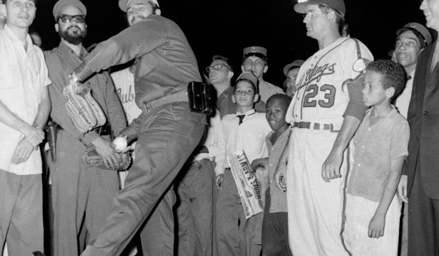 FILE - In this April 20, 1960, file photo, Cuban leader Fidel Castro tosses the traditional first ball at ceremonies opening the International League baseball season, in Havana, Cuba. At right is Rochester Red Wings manager Clyde King, whose Redwings met the 1959 Little World Series champion Havana Sugar Kings, in the season opener. In June, 1960 the Red Wings were the last American ball club to play a regulation game in Cuba until the Baltimore Orioles played an exhibition game in Havana in 1999. It's too soon to tell what impact the normalizing of relations between the U.S. and Cuba might have on the game. (AP Photo/File)