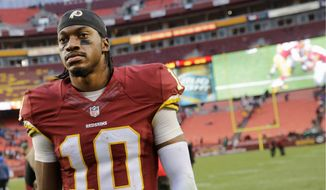Tough: Washington Redskins quarterback Robert Griffin III has struggled with injuries and coach Jay Gruden's offense. It wasn't until Saturday that he achieved his first victory in a complete game since midway through last season. (Associated Press photographs)