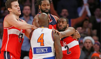 Wizards forwards Kris Humphries (left) and Nene Hilario restrain New York Knicks forward Quincy Acy and Wizards guard John Wall (2) after they engaged in an on-court scuffle in the second half on Thursday at Madison Square Garden. Acy was ejected from the game Wall received a technical foul. (Associated Press Photographs)