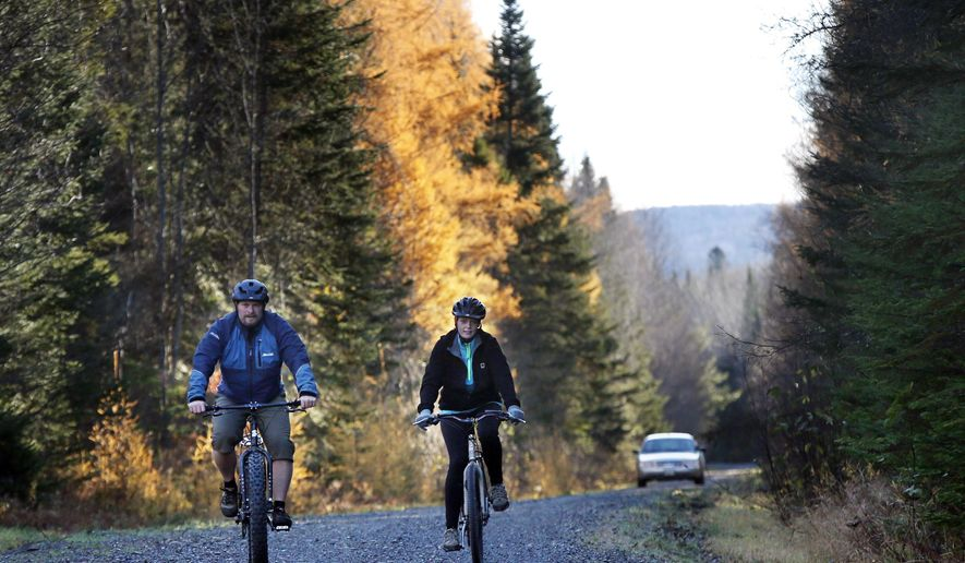 FILE - In this Oct. 30, 2014 file photo, nurse Kaci Hickox, right, and her boyfriend, Ted Wilbur are followed by a Maine State Trooper as they ride bikes on a trail near their home in Fort Kent, Maine. State officials went to court to try to keep Hickox in quarantine for a 21-day incubation period after she returned from Africa where she treated patients with Ebola. Republican victories on Election Day, a fire that claimed six lives and Hickox are the top stories of the year in Maine. (AP Photo/Robert F. Bukaty, File)