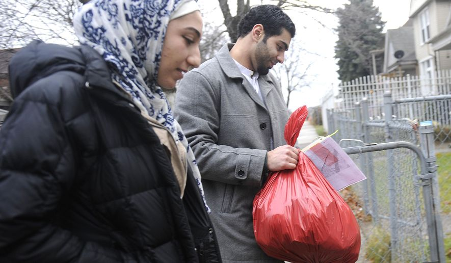 Ranim Suliman and Tarik Baraka, both of West Bloomfield, Mich., deliver a bag of holiday goodies to a home in southwest Michigan, Thursday, Dec. 25, 2014. (AP Photo/Detroit News, Elizabeth Conley)  DETROIT FREE PRESS OUT; HUFFINGTON POST OUT