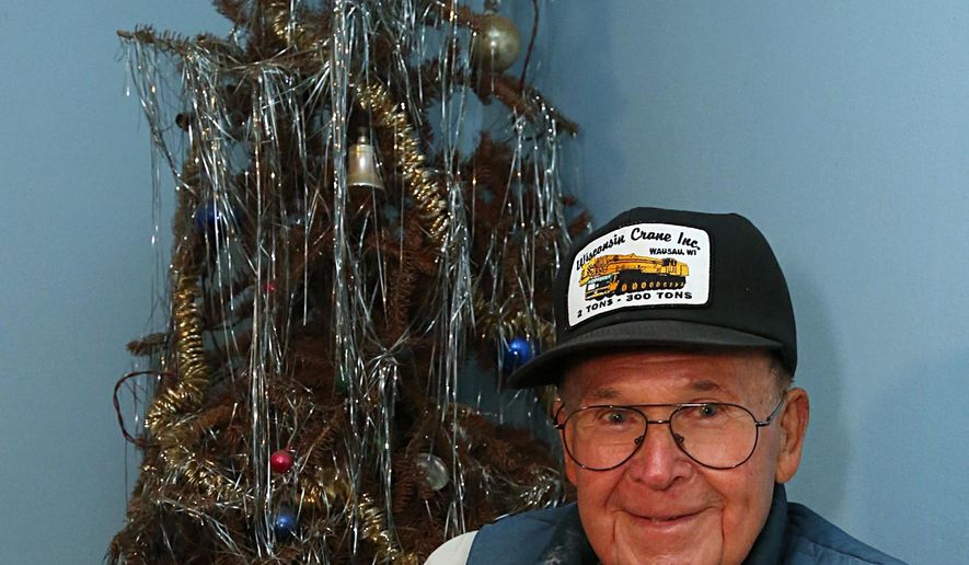 Neil Olson of Wausau, Wis., sits, Oct. 17, 2014, in front of the Christmas tree that has been in his living room since 1979. He is planning on keeping it up until all his sons can gather with him at his home. (AP Photo/Daily Herald, Dan Young)