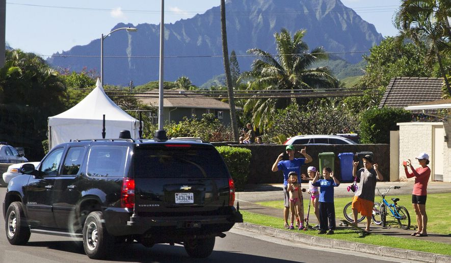 A group of children and adults wave as the motorcade carrying President Barack Obama and the first family from their rental home for a beach visit passes by Thursday, Dec. 25, 2014, in Kailua, Hawaii during the Obama family vacation. (AP Photo/Jacquelyn Martin)