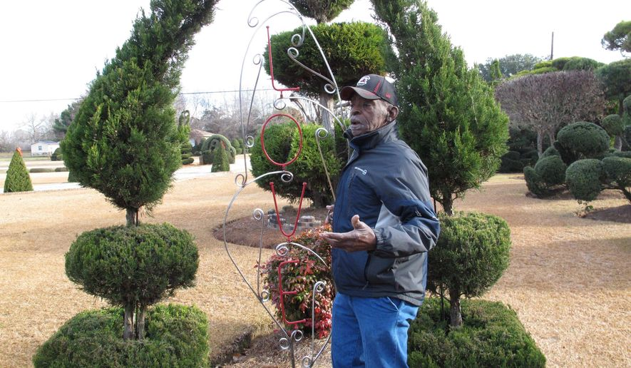 "In this Dec. 11, 2014 photo, Pearl Fryar talks about one of many sculptures in his famous topiary garden, in Bishopville, S.C. The theme of the garden is ""Love, Peace and Goodwill"" and instead of sculpting trees and bushes into animas, Fryar makes abstract creates he says follow the true structure of the plant.  (AP Photo/Jeffrey Collins)"