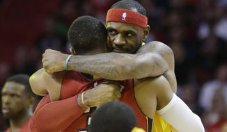 Cleveland Cavaliers forward LeBron James, right, hugs Miami Heat guard Dwyane Wade before an NBA basketball game, Thursday, Dec. 25, 2014, in Miami. (AP Photo/Lynne Sladky)