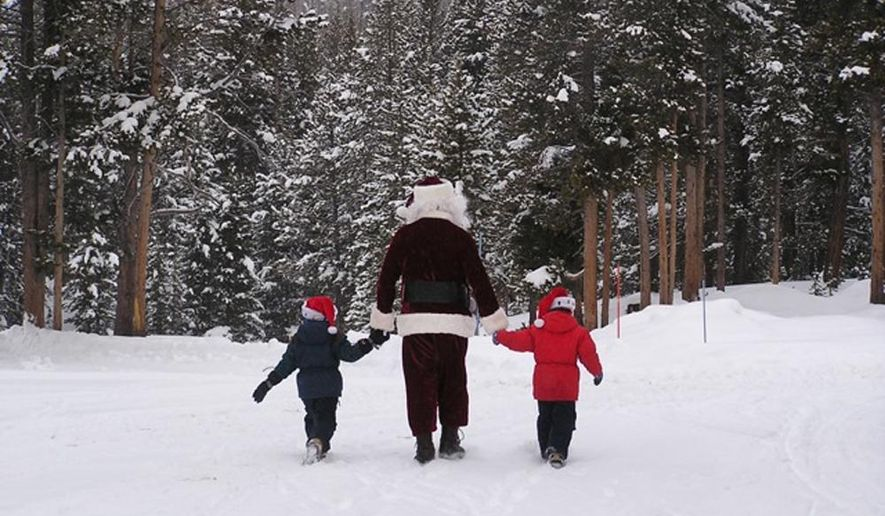 In this 2009 picture provided by Yellowstone National Park, Santa holds hands with Hart and Ellie Vandzura in the Canyon Village area of Yellowstone National Park on Christmas Day. This Christmas marks a 25-year tradition of Santa delivering gifts to the children of park employees working in Yellowstone over winter. (AP Photo/Yellowstone National Park)