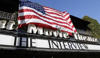 """The Interview,"" the comedy starring Seth Rogen and James Franco, is listed under an American flag on the marquee of the Cinefamily at Silent Movie Theater in Los Angeles, Thursday, Dec. 25, 2014. The film's Christmas Day release was canceled by Sony after threats of violence by hackers linked to North Korea, but the release was reinstated in some independent theaters and through a variety of digital platforms.(AP Photo/Richard Vogel)"