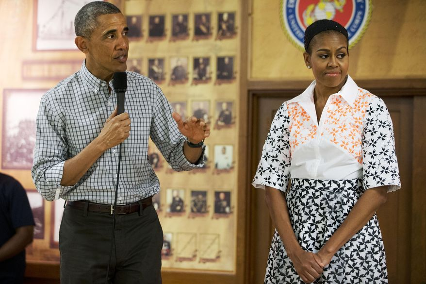 President Barack Obama, with first lady Michelle Obama, speaks to troops and their families on Christmas Day, Thursday, Dec. 25, 2014, at Marine Corps Base Hawaii in Kaneohe Bay, Hawaii during the Obama family vacation. (AP Photo/Jacquelyn Martin)