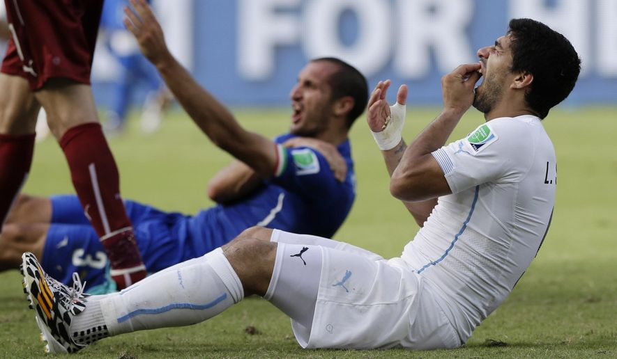 FILE - In this June 24, 2014, file photo, Uruguay's Luis Suarez holds his teeth after running into Italy's Giorgio Chiellini's shoulder during a group D World Cup soccer match in Natal, Brazil. Perhaps odder things happened in sports in 2014, but for sheer audacity, and on a global stage no less, the bite by Suarez takes the (temporary porcelain) crown. (AP Photo/Ricardo Mazalan, File)