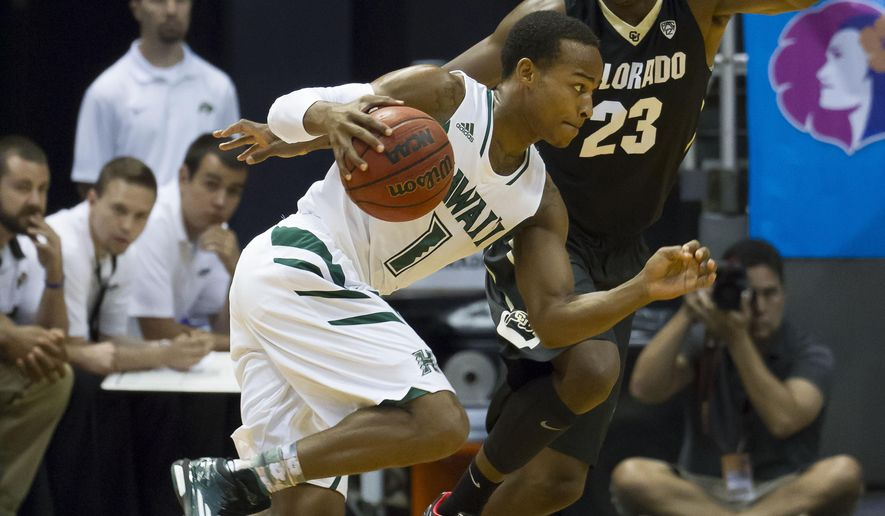 Hawaii guard Garrett Nevels (1) attempts to get by Colorado guard Jaron Hopkins (23) in the first half of an NCAA college basketball game at the Diamond Head Classic on Thursday, Dec. 25, 2014, in Honolulu. (AP Photo/Eugene Tanner)