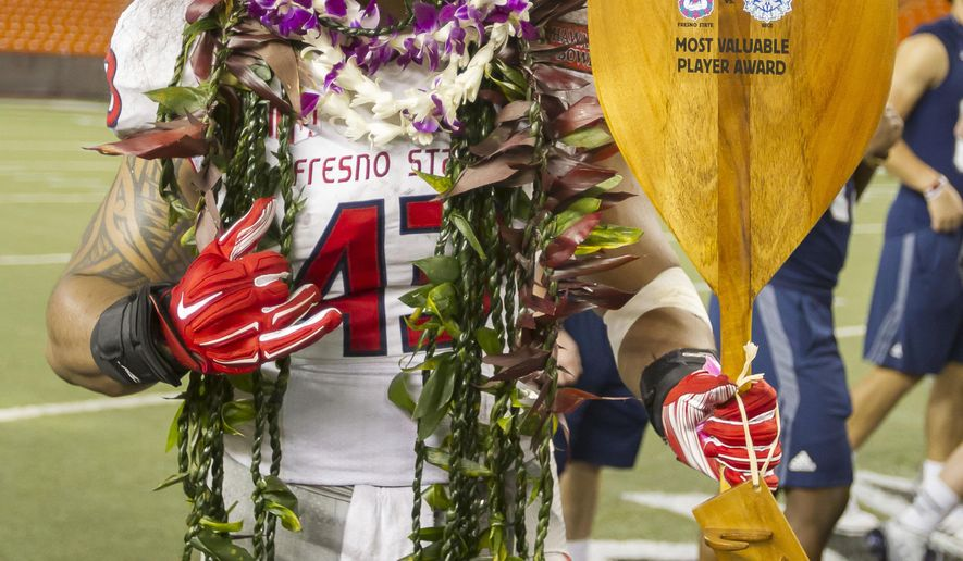 Fresno State linebacker Karl Mickelsen, stands with the most valuable player award in the Hawaii Bowl NCAA college football game against Rice, Wednesday, Dec. 24, 2014, in Honolulu. (AP Photo/Eugene Tanner)