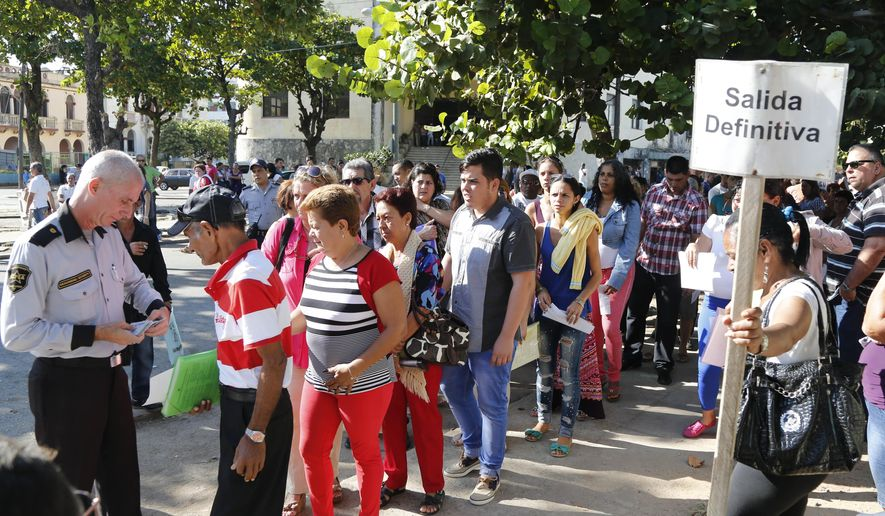 "People queue for visas at the U.S. Interests Section in Havana, Cuba, Monday, Dec. 22, 2014. After the surprise announcement of the restoration of diplomatic ties between Cuba and the U.S., many Cubans expressed hope that it will mean greater access to jobs and the comforts taken for granted elsewhere, and lift their struggling economy. The sign on the post reads in Spanish ""definite Exit."" (AP Photo/Desmond Boylan)"