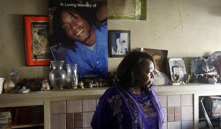 In this Dec. 23, 2014 photo, Lorrain Taylor stands in front of an image of Diamond Jackson, who was shot and killed in his neighborhood in 2009, in Oakland, Calif. Taylor was paying a visit to Jackson's family as part of her duties for the nonprofit 1000 Mothers Against Violence. (AP Photo/Marcio Jose Sanchez)