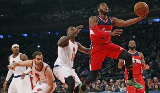 Washington Wizards guard John Wall (2) goes up for a layup after breaking through  the defense of New York Knicks guard Jose Calderon (3) and Knicks center Samuel Dalembert (11) in the first half of an NBA basketball game at Madison Square Garden in New York, Thursday, Dec. 25, 2014. (AP Photo/Kathy Willens)