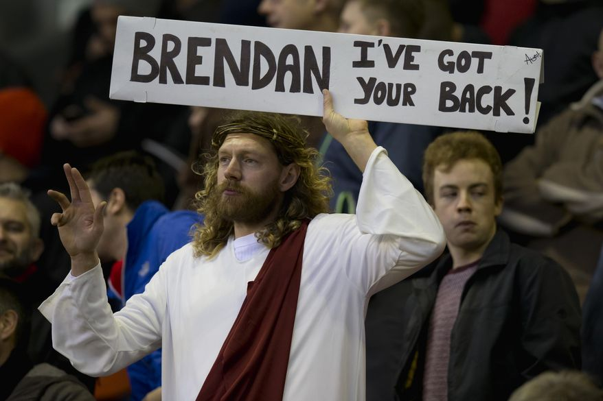 A Liverpool supporter dressed in the stereotypical image of Jesus holds up a sign supporting manager Brendan Rodgers before the team's English Premier League soccer match against Arsenal at Anfield Stadium, Liverpool, England, Sunday Dec. 21, 2014. (AP Photo/Jon Super)